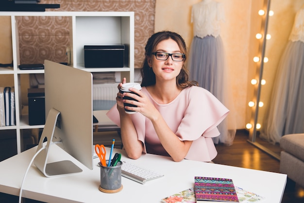 Młoda stylowa seksowna kobieta w różowej luksusowej sukience, letni trend, elegancki styl, projektant mody pracuje w biurze na komputerze