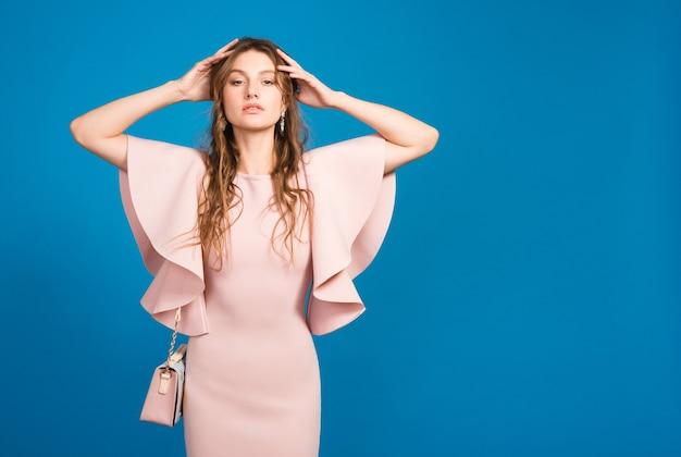 Młoda stylowa seksowna kobieta w różowej luksusowej sukience, letni trend w modzie, elegancki styl, niebieskie tło studio, trzymając modną torebkę