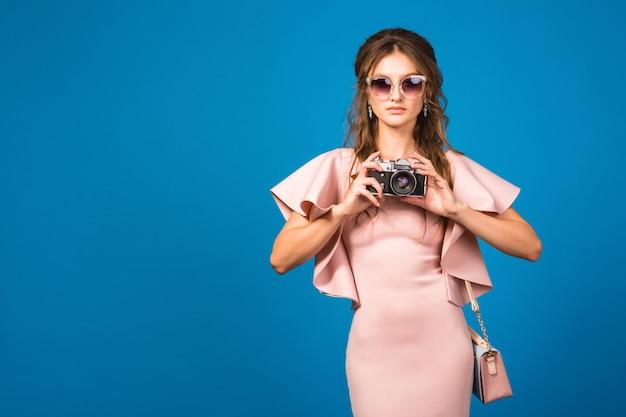 Młoda stylowa seksowna kobieta w różowej luksusowej sukience, letni trend w modzie, elegancki styl, okulary przeciwsłoneczne, robienie zdjęć aparatem vintage