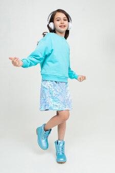 Młoda stylowa, urocza dziewczyna w turkusowej bluzce i butach słucha muzyki na słuchawkach i tańczy w studiu o białych ścianach.