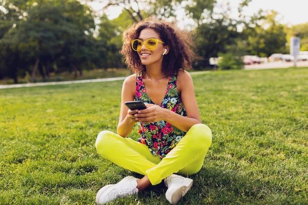 Młoda stylowa uśmiechnięta czarna kobieta za pomocą smartfona, słuchanie muzyki na bezprzewodowych słuchawkach, zabawy w parku