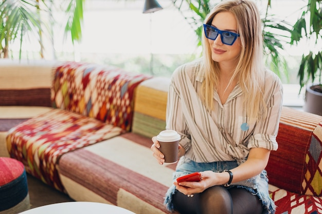 Młoda stylowa uśmiechnięta kobieta siedzi w kawiarni hipster na kanapie na sobie koszulę i niebieskie okulary, picie kawy