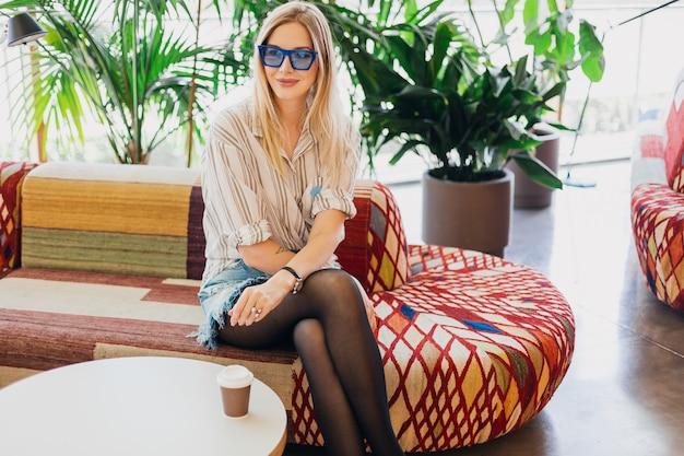 Młoda stylowa uśmiechnięta kobieta siedzi w kawiarni hipster na kanapie na sobie koszulę i niebieskie okulary przeciwsłoneczne