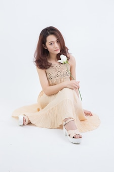 Młoda stylowa zmysłowa kobieta z długimi brązowymi włosami na sobie żółty siedzi i pozowanie na białym tle