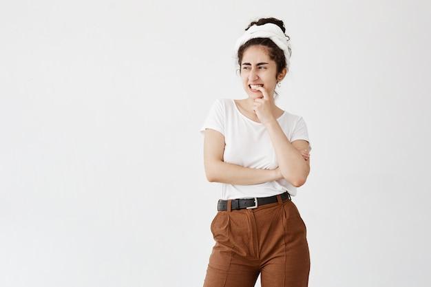 Młoda suczka o ciemnych i falowanych włosach ma przemyślany wyraz twarzy, trzyma palec na ustach, wygląda na bok, myśląc o czymś ważnym, pozuje na białej ścianie z miejsca na kopię tekstu promocyjnego