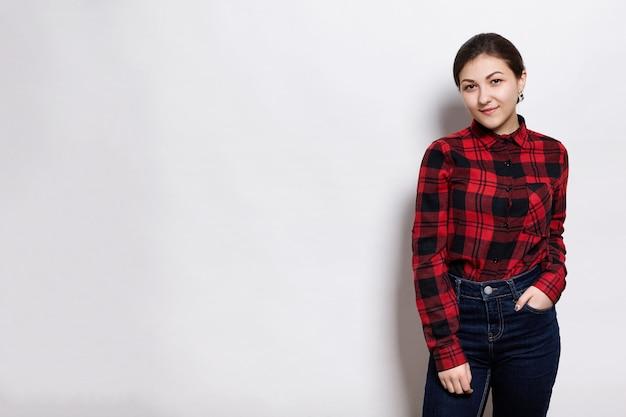 Młoda sylish hipster dziewczyna w czerwonej koszuli w kratę i dżinsy, trzymając ją za rękę