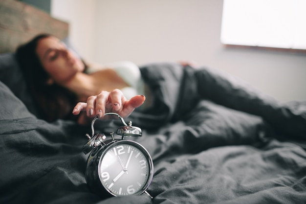 Młoda sypialna kobieta i budzik w sypialni w domu. dziewczyna zaspała w łóżku i zszokowała budzika