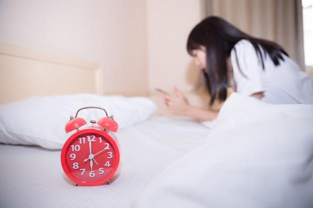 Młoda sypialna kobieta i budzik w sypialni w domu