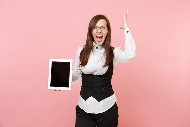 Młoda szalona kobieta biznesu w okularach krzyczy trzymać komputer typu tablet pc z pustym pustym ekranem rozprzestrzeniania ręce na białym tle na różowym tle. szefowa. koncepcja bogactwa kariery osiągnięcia. skopiuj miejsce.