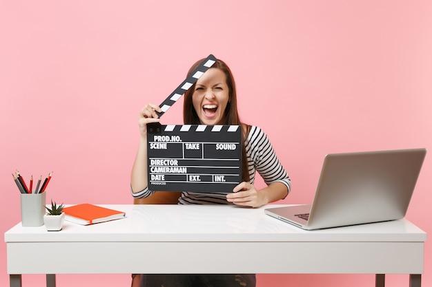 Młoda szalona kobieta krzyczy trzymając klasyczny czarny film robiąc klaps i pracując nad projektem, siedząc w biurze z laptopem
