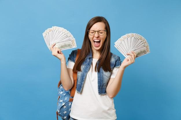 Młoda szalona studentka kobieta w okularach z plecakiem z zamkniętymi oczami krzyczy trzymać pakiet wiele dolarów, pieniądze w gotówce na białym tle na niebieskim tle. edukacja w koncepcji liceum uniwersyteckiego.