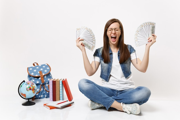 Młoda szalona studentka krzyczy rozkładając ręce trzymając pakiet wiele dolarów, pieniądze w gotówce siedzą w pobliżu plecaka na świecie, książki na białym tle