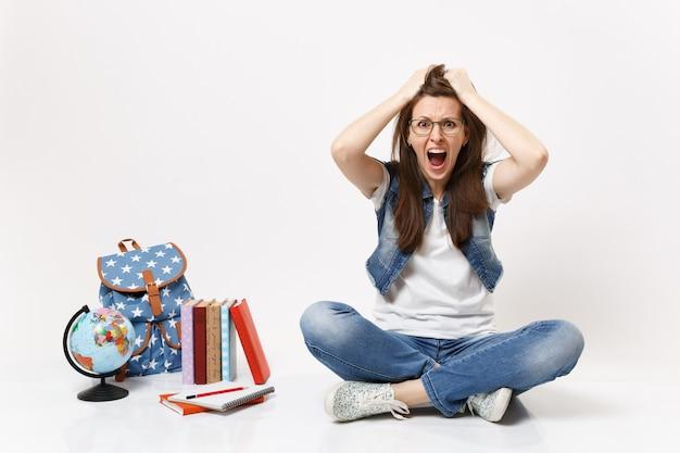 Młoda szalona studentka z zawrotami głowy w dżinsowych ubraniach krzyczy, trzymając się głowy, siedząc w pobliżu kuli ziemskiej, plecak szkolny na białym tle