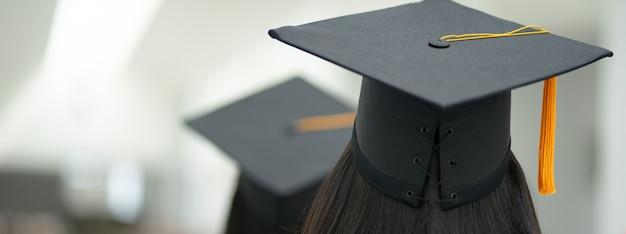 Młoda szczęśliwa absolwentka uniwersytetu azjatyckiego kobieta w sukni ukończenia szkoły i czapkę w kampusie uczelni. edukacja pień fotografia