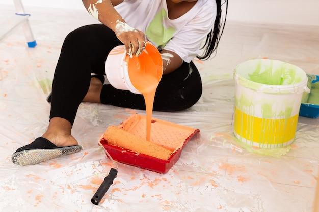 Młoda szczęśliwa african american kobieta maluje ścianę wewnętrzną wałkiem do malowania w nowym domu. kobieta