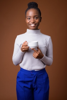 Młoda szczęśliwa afrykańska kobieta zulu trzymając filiżankę kawy podczas uśmiechu
