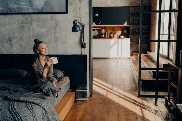 Młoda szczęśliwa atrakcyjna dziewczyna siedzi na łóżku w satynowej piżamie w pozycji lotosu z filiżanką gorącej kawy w dłoni, patrząc w stronę okna, uśmiechając się w porannym słońcu, ciesząc się weekendem w domu