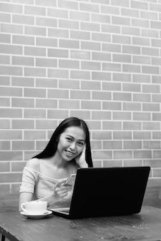 Młoda szczęśliwa azjatycka dziewczyna za pomocą telefonu z laptopem i cappuccino na drewnianym stole na ścianie z cegły