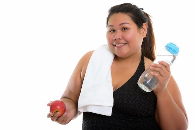 Młoda szczęśliwa azjatycka gruba kobieta uśmiecha się trzymając czerwone jabłko i butelkę wody