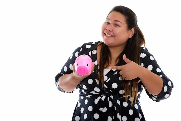 Młoda szczęśliwa azjatycka gruba kobieta uśmiecha się trzymając skarbonkę