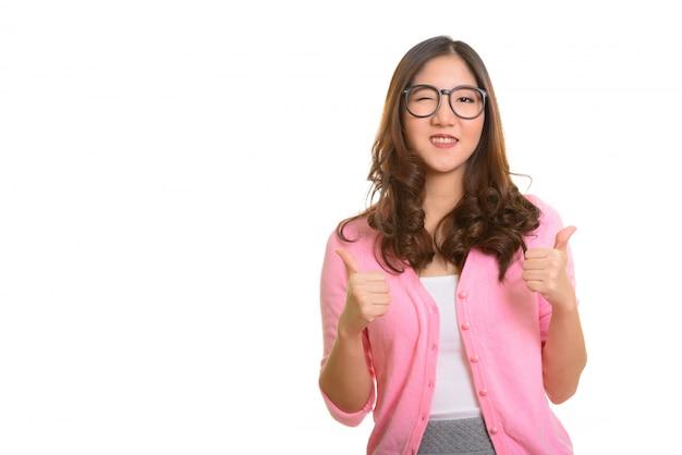 Młoda szczęśliwa azjatycka kobieta daje kciuki i mrugając odizolowane od białego