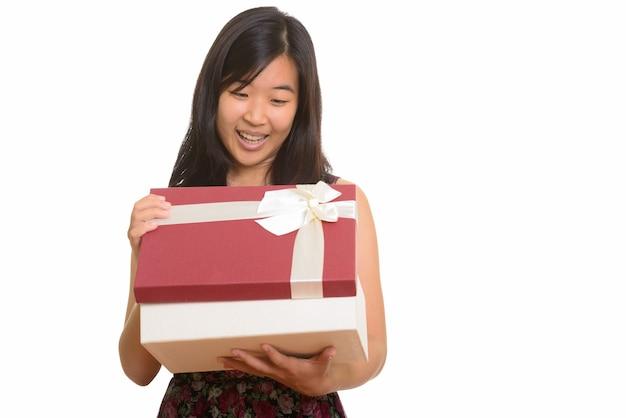 Młoda szczęśliwa azjatycka kobieta otwiera pudełko na prezent na białym tle