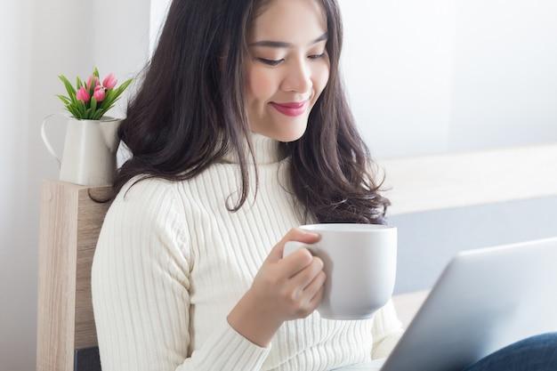 Młoda szczęśliwa azjatycka kobieta pracuje na swoim laptopie