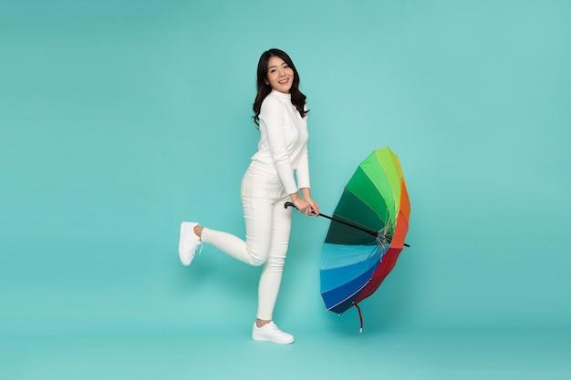 Młoda szczęśliwa azjatycka kobieta trzyma kolorowy parasol na białym tle na zielonym tle