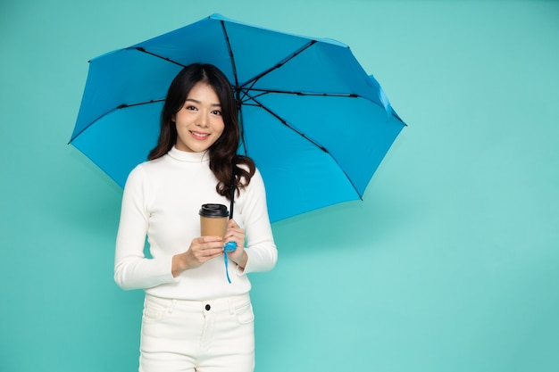 Młoda szczęśliwa azjatycka kobieta trzyma niebieski parasol i filiżankę gorącej kawy na zielonym tle