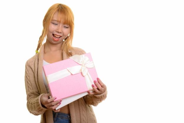 Młoda szczęśliwa azjatycka kobieta uśmiecha się i otwiera pudełko