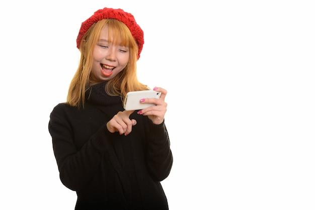Młoda szczęśliwa azjatycka kobieta uśmiecha się i używa telefonu komórkowego