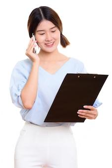 Młoda szczęśliwa azjatycka kobieta uśmiecha się podczas czytania w schowku i rozmawia przez telefon komórkowy