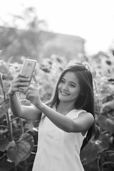 Młoda szczęśliwa azjatycka kobieta uśmiecha się podczas robienia zdjęcia selfie telefonem komórkowym w polu kwitnących słoneczników