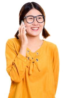 Młoda szczęśliwa azjatycka kobieta uśmiecha się podczas rozmowy przez telefon komórkowy