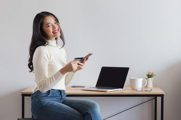 Młoda szczęśliwa azjatycka kobieta używa smartfona