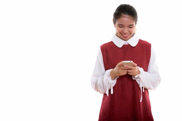 Młoda szczęśliwa azjatycka kobieta używa telefonu