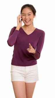 Młoda szczęśliwa azjatycka nastolatka uśmiecha się i rozmawia przez telefon komórkowy