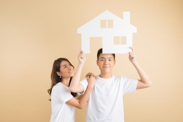 Młoda szczęśliwa azjatycka para przedstawia symbole dom