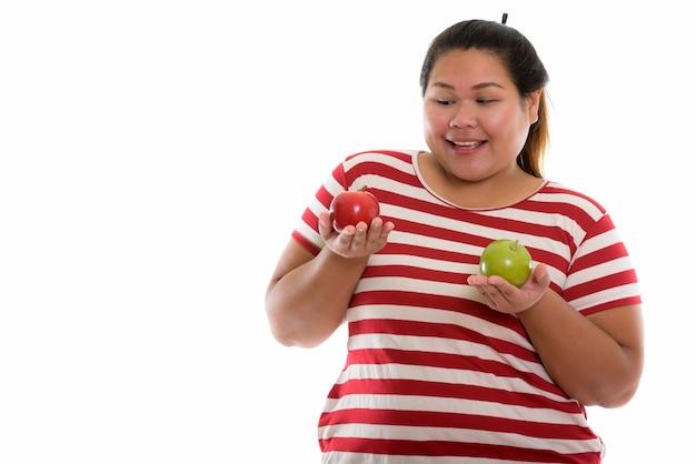 Młoda szczęśliwa azjatycka tłuszczu kobieta uśmiecha się trzymając jabłka