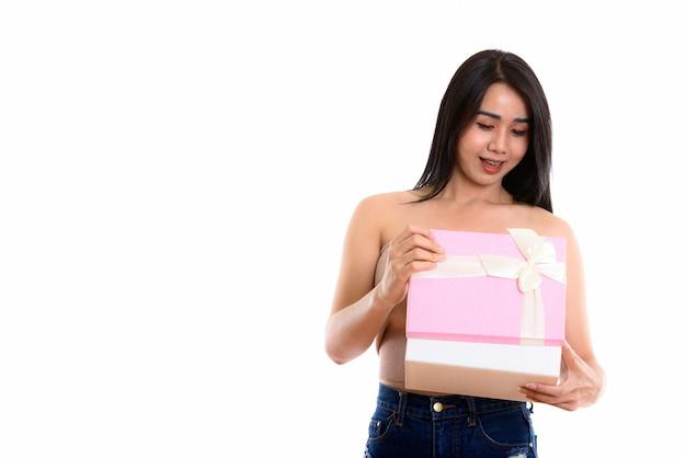 Młoda szczęśliwa azjatycka transseksualna kobieta uśmiecha się podczas otwierania pudełka