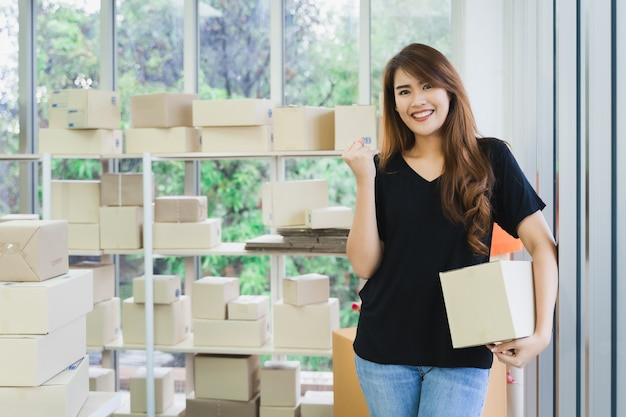 Młoda szczęśliwa azjatykcia biznesowa kobieta niesie pakuneczka pudełko pakuje i pokazuje biznesowego sukces