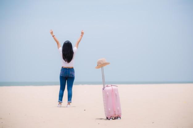 Młoda szczęśliwa azjatykcia dziewczyna przy plażą