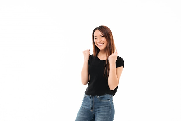 Młoda szczęśliwa azjatykcia dziewczyna w przypadkowej odzieży pokazuje zwycięzcy gest, patrzeje kamerę