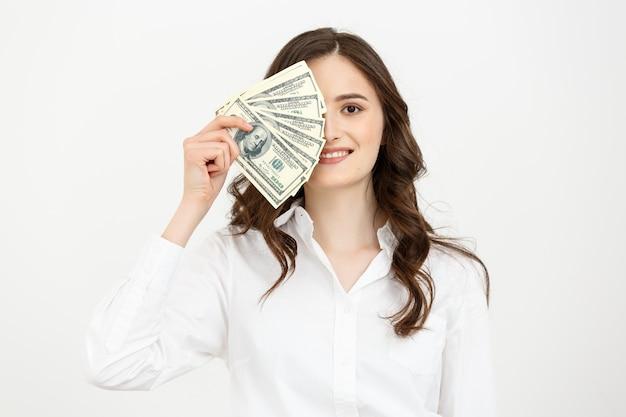 Młoda szczęśliwa biznesowa kobieta z dolarami w ręku odizolowywającymi