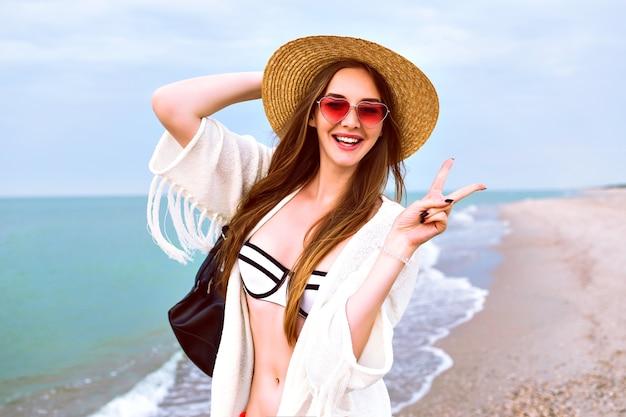 Młoda szczęśliwa blondynka pozuje na plaży, nosi słomkowy kapelusz i słodkie okulary przeciwsłoneczne w kształcie serca, cieszy się wakacjami w pobliżu oceanu, ubrana w bikini i kurtkę boho.