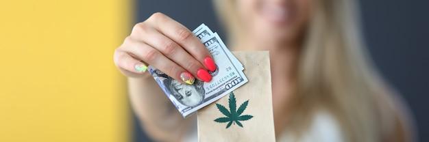 Młoda szczęśliwa blondynka trzymająca paczkę z marihuaną i dostawą legalnej marihuany