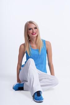 Młoda szczęśliwa blondynka ubrana w sportową siedzi relaksujący uśmiechnięty na białym tle