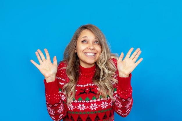 Młoda szczęśliwa blondynka w czerwonym świątecznym swetrze z jeleniem unosi ręce na niebieskim tle