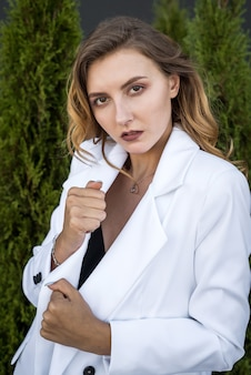 Młoda szczęśliwa brunetka kobieta w białym garniturze pozowanie w przyrodzie, biały cedr, czas letni