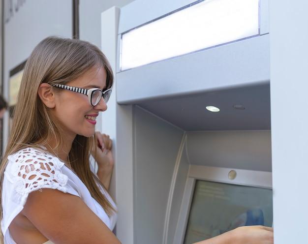 Młoda szczęśliwa brunetki kobieta wycofuje pieniądze od kredytowej karty